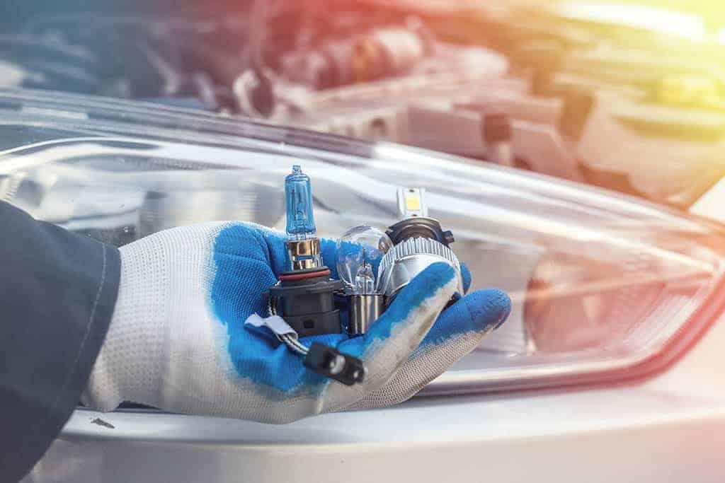 mechanic holding led lightbulb, hid lightbulb, and halogen lightbulb in our shop in Mays Landing, NJ