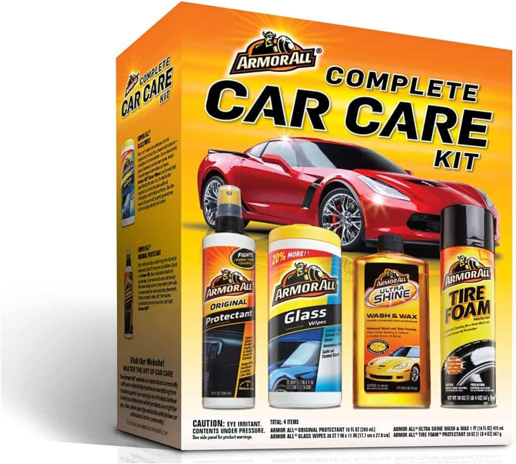 """A product image featuring Armor All's complete car kit box that contains a can of sprayable tire foam, a bottle of """"ultra shine wash & wax,"""" a container of glass wipes, and a spray bottle labeled """"original protectant"""" for use in the car's interior."""