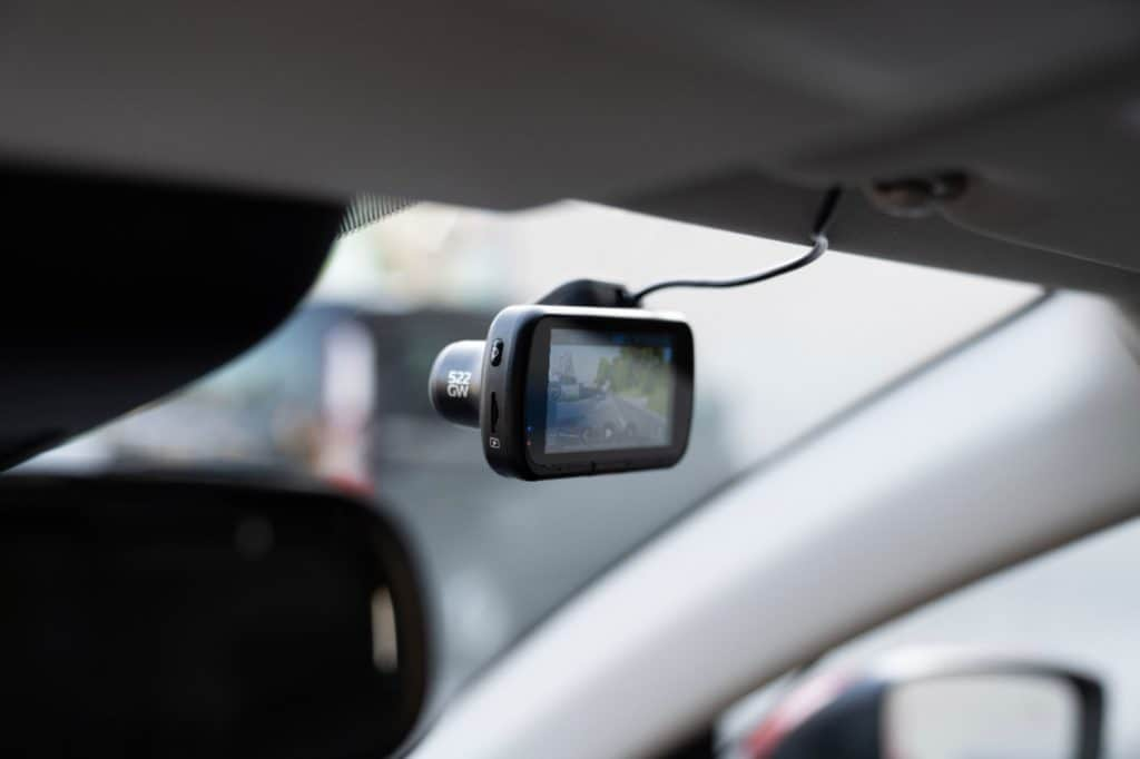 A product image for a dashboard camera to be used in cars; the image shows the dashcam mounted from the ceiling of the car facing forward out the windshield.
