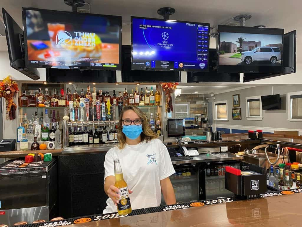 A woman wearing a facemask and holding a corona beer out towards the camera, standing behind a bar with three televisions above hear head and a wide variety of alcoholic beverages shown behind her.