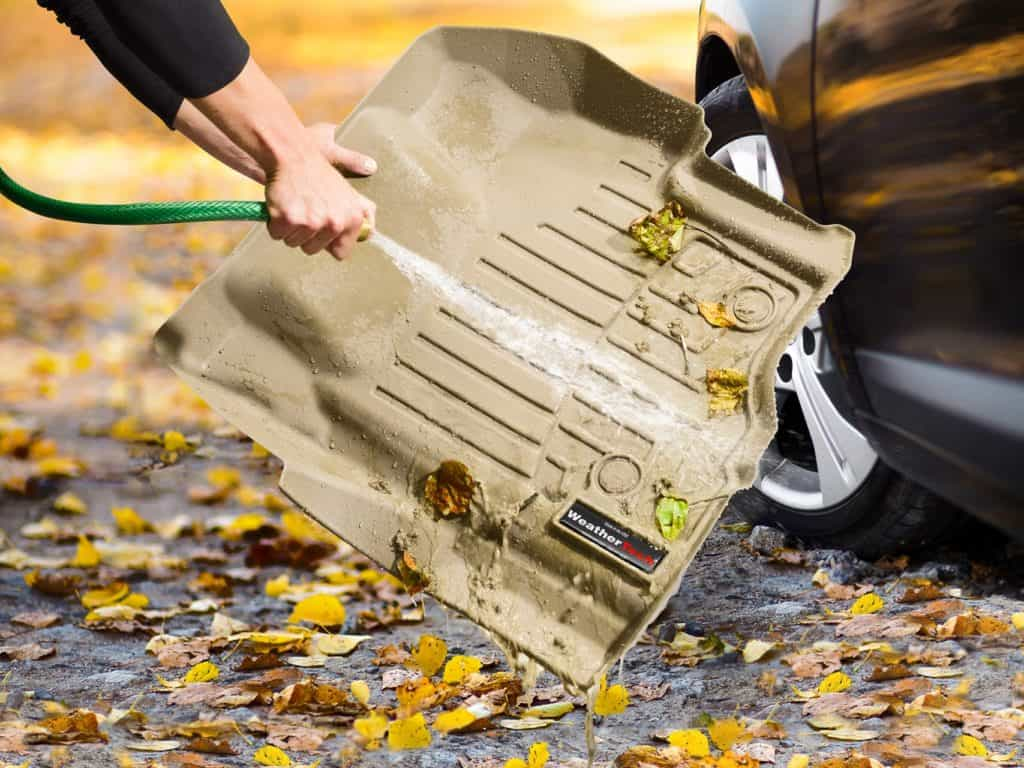 A product image for an easy-clean floor mat, featuring an action shot of a person spraying a hose on the product to wash leaves and dirt onto the ground. The vehicle is seen partially on the right side to demonstrate the purpose of the product.