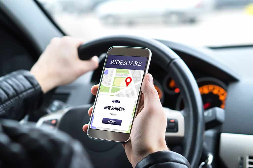 Ride share driver in car using the Uber or Lift app in mobile phone to pick up new customers in Atlantic City, NJ